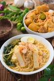 Tallarines del curry de Singapur o mee famosos del laksa con las decoraciones en b Foto de archivo