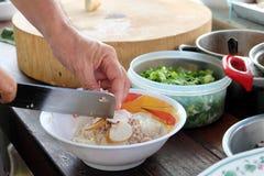 Tallarines el cocinar, del cerdo con la sopa de la bola de pescados, caliente y amarga Fotos de archivo