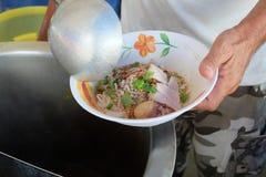 Tallarines el cocinar, del cerdo con la sopa de la bola de pescados, caliente y amarga Fotos de archivo libres de regalías