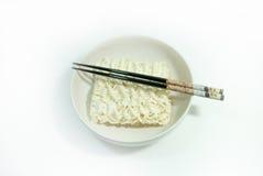 Tallarines en un cuenco en un fondo blanco Imagen de archivo