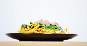 Tallarines fritos curruscantes con el cerdo empapado en salsa foto de archivo libre de regalías