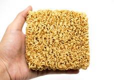 Tallarines inmediatos de los ramen asiáticos en manos en el backgroun blanco Imagen de archivo libre de regalías