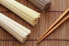 Tallarines japoneses con los palillos en la servilleta de bambú Fotografía de archivo