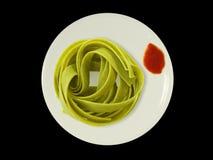 Tallarines verdes en una placa con la salsa de tomate aislada Imagen de archivo