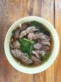 Tallarines y verduras cocidos, sopa fragante de la carne de vaca en una taza de fondo, pisos de madera fotografía de archivo