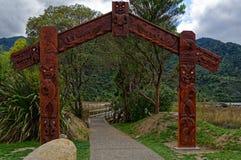 Tallas maoríes tradicionales en la entrada a Abel Tasman National Park de Nueva Zelanda foto de archivo