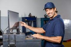 Taller de reparaciones de Using Computer In del mecánico feliz fotos de archivo