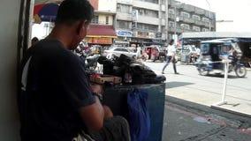 Taller de reparaciones del zapato al aire libre ocupado, hombre maduro que cose manualmente el zapato almacen de video