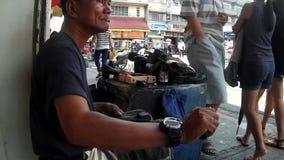 Taller de reparaciones del zapato al aire libre ocupado, hombre maduro que cose manualmente el zapato almacen de metraje de vídeo
