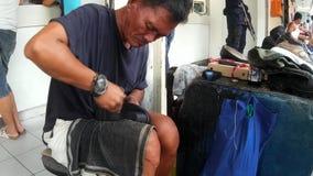 Taller de reparaciones del zapato al aire libre ocupado, hombre maduro que cose manualmente el zapato metrajes