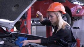 Taller del coche, nivel de aceite auto feliz de los controles del reparador del trabajador de mujer durante mantenimiento del aut almacen de video
