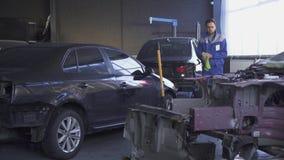 Taller grande interior del servicio del coche con el equipo moderno y coches estrellados después de un accidente en el centro del almacen de metraje de vídeo