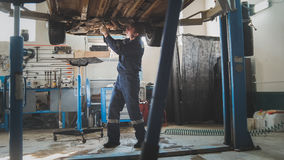 Taller mecánico del garaje - parte inferior de la situación auto levantada automotriz en servicio del automóvil fotografía de archivo