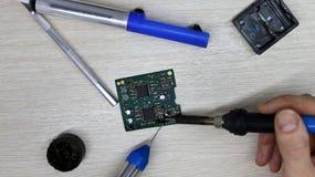 Taller sobre la reparación de los aparatos electrodomésticos, de la electrónica y de los procesadores soldador del tablero que su imagenes de archivo