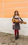 TALLIN, ΕΣΘΟΝΊΑ - CIRCA 2016: Ένας θηλυκός μουσικός οδών παίζει το nyckelharpa σε έναν πάροδο στην παλαιά πόλη Tallin στην Εσθονί Στοκ Φωτογραφία