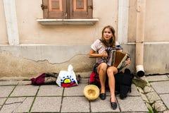 TALLIN, ESTLAND - CIRCA 2016: Een vrouwelijke straatmusicus speelt de harmonika op een zijgang in de oude stad van Tallin in Estl stock foto