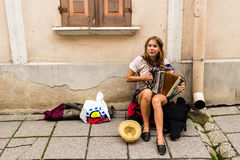 TALLIN, ESTONIA - CIRCA 2016: A female street musician plays the accordion on a side walk in the old town of Tallin in Estonia. TALLIN, ESTONIA - CIRCA 2016: A Stock Photo