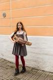 TALLIN, ESTONIA - CIRCA 2016: Un músico de la calle de la hembra juega el nyckelharpa en un paseo lateral en la ciudad vieja de T foto de archivo