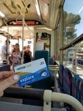 Мальтийсная карточка Tallinja перехода в руке ` s девушки в шине с пассажирами стоковые фотографии rf