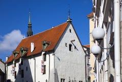 Tallinn, construção do século XVII na cidade e nas bandeiras velhas com as brasões das cidades antigas do unio Hanseatic Imagens de Stock Royalty Free