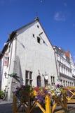 Tallinn, de bouw van de 17de eeuw in de oude stad en de vlaggen met de wapenschilden van de oude steden van Hanseatic unio Stock Afbeeldingen