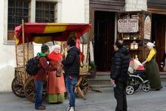 TALLINN ESTLAND - APRIL 11, 2017: Turister i gammal stad Säljare av mandelmuttrar i nationella medeltida klänningar Fotografering för Bildbyråer