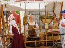 TALLINN ESTLAND - JULI 8, 2006: Turister i gammal stad Säljare av mandelmuttrar i nationella medeltida klänningar Arkivbilder