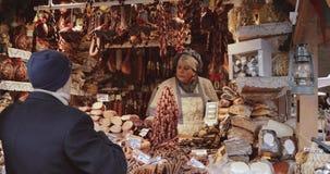 Tallinn, Estonia - 22 de diciembre de 2017: El vendedor de la mujer en mercado tradicional de la Navidad vende la salchicha y otr almacen de video