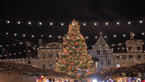 Tallinn, Estonia-December 25,2017: Holiday Fair With Christmas Tree Illuminated. Tallinn, Estonia-December 25, 2017: Winter celebration city fair in the old town stock footage
