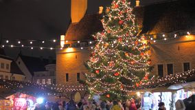 Tallinn, Estonia-December 25,2017: Holiday Fair With Christmas Tree Illuminated. Tallinn, Estonia-December 25, 2017: Winter celebration city fair in the old town stock video