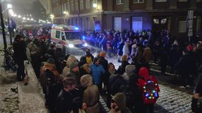Crowded Tallinn Harju street. After New Years celebration, Ambulance drives through the crowd of people stock video footage