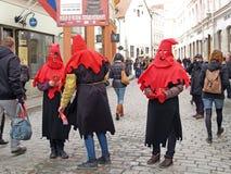 Tallinn, Estonia Los hombres jovenes en los trajes de verdugos medievales distribuyen a los transeúntes prospectos en la calle de fotografía de archivo