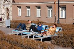 Tallinn, Estonia, 05/02/2017 people lie on a bench and enjoy the royalty free stock image