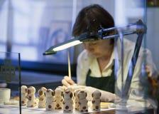TALLINN, ESTONIE 17 JUIN - 2012 : la femme peint des chiffres dans la boutique au musée des marzipans Images stock