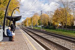 Elderly woman sits on platform of train station. TALLINN, Nomme, ESTONIA - OCTOBER 19, 2017: View of the railway station on an autumn sunny day royalty free stock photo