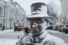 Tallinn, sculpture in bronze chimney sweeper. Estonia, Tallinn, sculpture in bronze chimney sweep in the center of town. Close up. Winter. Covered by snow. on Royalty Free Stock Image