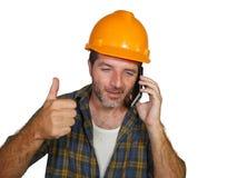 tallking与手机的满意的顾客的愉快的高效率和快乐的工作员或承包商人佩带的建造者帽子 库存照片