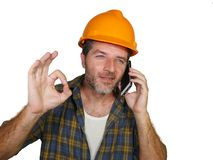 tallking与手机的满意的顾客的愉快的高效率和快乐的工作员或承包商人佩带的建造者帽子 免版税库存照片