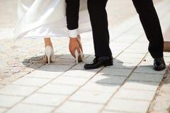 Tallone di nozze attaccato nella piccola lacuna sulla pavimentazione - lo sposo sta aiutando - del momento maldestro prima di cer fotografia stock