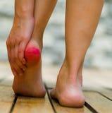 Tallone rosso a causa di dolore, mano della donna che fa un certo massaggio Pavimento di legno immagine stock