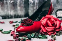 Talloni e rosa rossa rossi su fondo bianco e grigio Immagini Stock