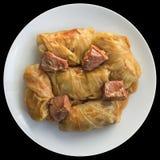 Tallrik av kål Rolls som är välfylld med köttfärs som lagas mat i tomatsås med rökt griskött Ham Chunks On Black Background arkivbilder
