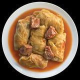 Tallrik av kål Rolls som är välfylld med köttfärs som lagas mat i tomatsås med rökt grisköttHam Chunks Isolated On Black bakgrund royaltyfria bilder