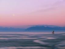 Tallship que cruza contra el contexto de la montaña en la salida de la luna Imagen de archivo libre de regalías