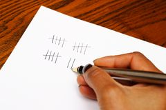 Tally. A womans hand making tally marks with a pen on a sheet of paper on a wooden table Royalty Free Stock Photos