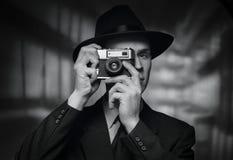 50-talman i hatten som tar en bild Arkivfoto