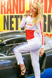 Talons hauts blonds de sourire de fille de Motorshow emballant le costume Photographie stock