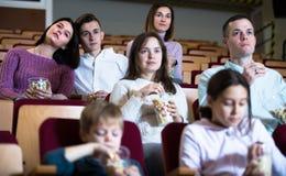Talrijk publiek die popcorn eten en op een film letten royalty-vrije stock afbeeldingen