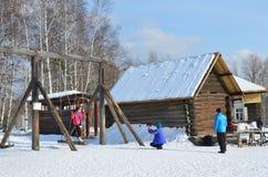 Taltsy, Irkutsk-Region, Russland, März, 02, 2017 Die Leute, die auf alten Russen fahren, schwingen in Architektur-ethnographische stockbilder