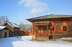 Taltsy, Irkutsk-Region, Russland, März, 02, 2017 Hölzerne Hütte und ein Fragment des Gemeindegefängnisses auf dem links Irkutsk A lizenzfreie stockfotos
